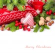 Textile checkered heart, nuts and red berries near knitted pillows and branches of a Christmas tree on a white background. A Christmas background with a place for the text. — Stockfoto #75842997