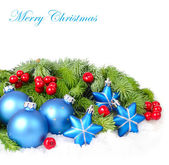 Blue Christmas balls and stars and red berries on branches of a Christmas tree on a white background. A Christmas background with a place for the text. — Stock Photo