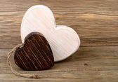 "Two wooden hearts on a wooden background. A background for the subject ""love"". — Stock Photo"