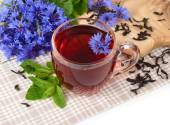 Transparent glass cup of black tea with mint and cornflowers on a white background. — Stock Photo