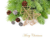 Golden metal openwork fir-tree and cones on branches of a Christmas tree on a white background. A Christmas background with a place for the text. — Stock Photo