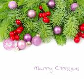 Violet Christmas balls and red berries on fluffy branches of a Christmas tree on a white background. A Christmas background with a place for the text. — Stock Photo