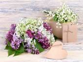 Fresh lilac, gift boxes and wooden heart (a place for the text) on a wooden background. A festive background with a place for the text. — Stock Photo