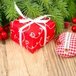 Red gift box, red berries and red checkered textile heart on a wooden background. A Christmas background with a place for the text. — Stockfoto #78241272