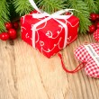 Red gift box, red berries and red checkered textile heart on a wooden background. A Christmas background with a place for the text. — Stockfoto #78559282