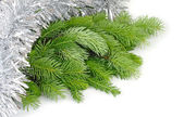 Fluffy branches of a Christmas tree in tinsel on a white background. — Stock Photo