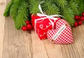 Red gift box and red checkered heart on branches of a Christmas tree on a wooden background. A Christmas background with a place for the text. — Stock Photo