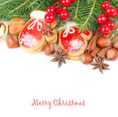 Ginger cookies in the form of mittens, nuts and red berries on branches of a Christmas tree on a white background. A Christmas background with a place for the text. — Stock Photo