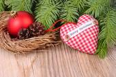 Red checkered textile heart and Christmas-tree decorations on branches of a Christmas tree on a wooden background. A Christmas background with a place for the text. — Stock Photo