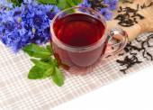Cup of black tea with mint and cornflowers on a linen napkin on a white background. — Stock Photo