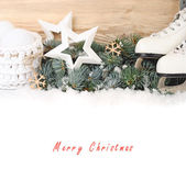 The skates, stars and white Christmas balls on branches of a snow-covered Christmas tree on a white background. A Christmas background with a place for the text. — Stock Photo