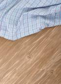 The checkered crumpled kitchen towel on a wooden background. — Stock Photo