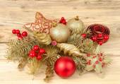 Christmas composition with golden and red Christmas-tree decorations on a light wooden background. — Stock Photo
