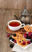 Cup of black tea, berry cookies and fresh raspberry and blackberry on a dark wooden background. Vertical format. — Stock Photo