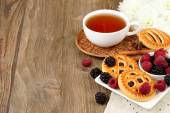 Cup of black tea, berry cookies and fresh raspberry and blackberry on a dark wooden background. Horizontal format. — Stock Photo