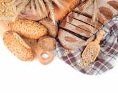 Fresh bread, ears and grain on  checkered napkin on a white background with a place for the text. — Stock Photo