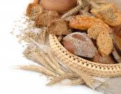 Fresh bread in a wattled basket, ears and grain on a white background with a place for the text. — Stock Photo