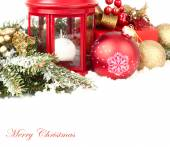 Christmas composition with a red small lamp candlestick and golden and red Christmas balls on snow-covered branches of a Christmas tree on a white background. A Christmas background with a place for the text. — Stock Photo