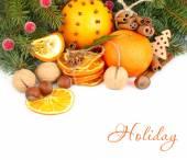 Сушеные апельсины, корицей и орехами на ветви елки на белом фоне. Новогодний фон с местом для текста. — Стоковое фото