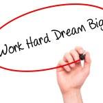 Постер, плакат: Man Hand writing Work Hard Dream Big with black marker on visual