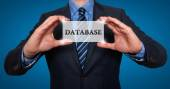 Businessman holds white card with Database sign  - Stock Photo — Stockfoto