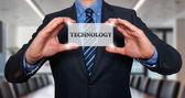 Businessman holds white card with Technology sign, Grey - Stock Photo — Stock Photo
