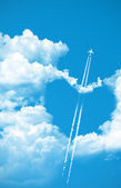 Airplane fly over a heart on the sky — Stock Photo