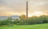 Factory building in sunset behind trees — Foto Stock