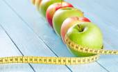 Apples with tape measure on blue wood background, lose weight concept — Stock Photo