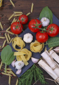 Pasta, tomatoes and herbs on a wooden board — Stock Photo