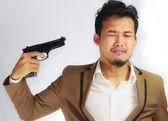 Młody biznesmen wskazując broń na głowę — Zdjęcie stockowe