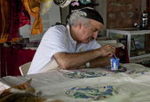 ISTANBUL, TURKEY - AUGUST 27, 2014: Batik artist painting in street market studio. — Stock Photo
