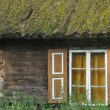Old wooden house with wooden shutters and thatched roof. Rural buildings. Poland. — Stock Photo #61844391