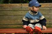 Boy in red rubber boots sitting on a rocking bench. Entangling Vines swing. — Stockfoto