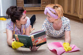 Two women reading a book lying on the floor — Stock Photo