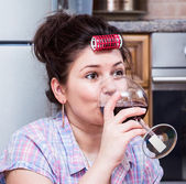 Woman in the kitchen drinking wine — Stock Photo