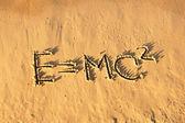 Einstein's formula handwriting on the sand. — Stock Photo