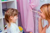 Mom paint brush nose daughter. — Stock Photo