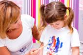 Mom draws paints on a T-shirt daughter. — Stock Photo