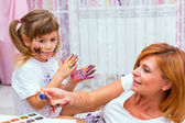 Mom draws paints on a T-shirt daughter lying on the floor. — Stock Photo