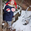 Cute child girl walking in winter snowy garden with christmas candy — Stock Photo #60615765