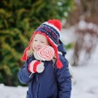 Cute child girl walking in winter snowy garden with christmas candy — Stock Photo #60615781