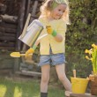 Cute blonde child girl plays little gardener and watering flowers in spring garden — Stock Photo #60616375
