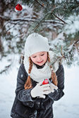 Cute child girl in grey coat and white hat, scarf and gloves plays with toy bullfinch in winter snowy forest — Stock Photo