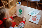 Child girl in knitted seasonal sweater  making christmas handprints post cards — Stock Photo