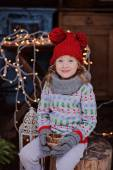 Cute child girl in christmas sweater and red hat sitting outdoor with lights and wooden candle holder — Stock Photo