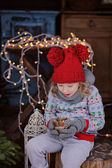 Cute child girl in christmas sweater and red hat with wooden candle holder and fir branches — Stock Photo