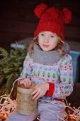 Cute child girl in christmas sweater and red hat sitting on wooden table with box of cones with lights on background — Stock Photo