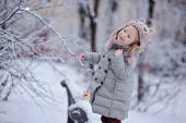 Cute happy child girl in owl hat and grey coat walking in snowy winter park — Stock Photo