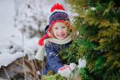 Happy child girl in red and blue knitted hat walking in winter snowy garden — Stock Photo
